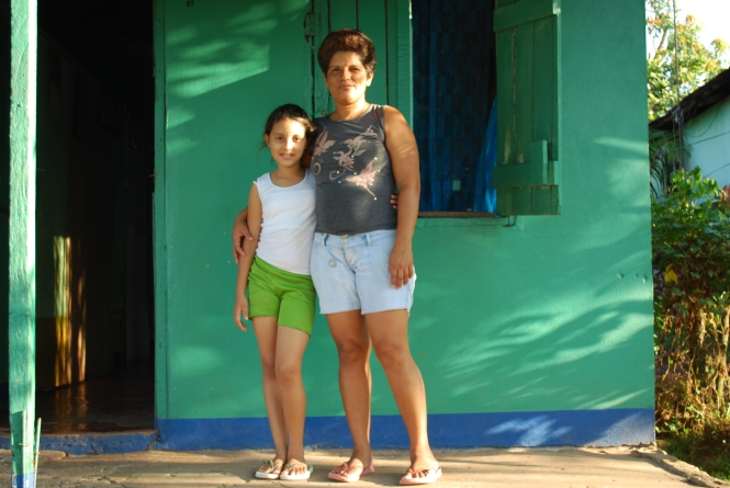 Debora stands with her daughter in front of their home.